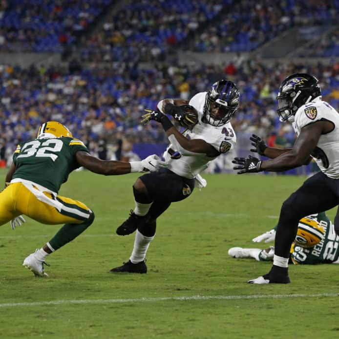 Ravens running back Justice Hill breaks tackle against Packers